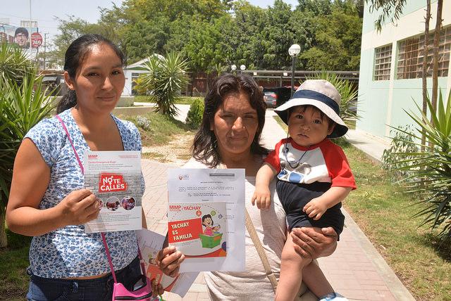 Mujeres mostrando folletos contra la violencia familiar